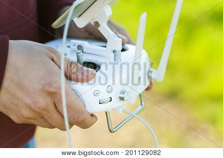 quadcopter flight outdoors, aerial imagery and tech hobby, recreation concept - closeup on pilot hands and white remote radio control, modern high-tech solution for joy of flying and filming quality