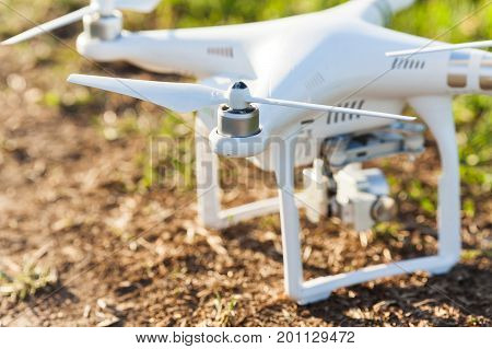 RUSSIA, ROSTOV-ON-DON - APRIL 20, 2017: closeup on white modern drone on earth surface, high-tech miracle is waiting for flight and shooting high-quality video