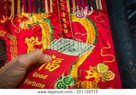 Chinese dragon decoration and a red envelope in hong bao.Is traditional to give money during the Chinese New Year in China.Envelope with the chinese words meaning Good fortune on it, and Dollar bills