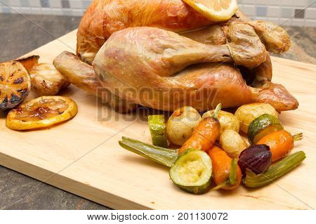 Lemon and garlic chicken Homemade Lemon and garlic Whole Chicken on a cutting board with vegetables