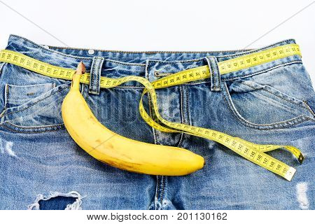 Kinky fruit on jeans pocket close up. Health and male sexuality concept. Mens pants with banana imitating male genitals selective focus. Jeans with measure tape instead of belt on white background.