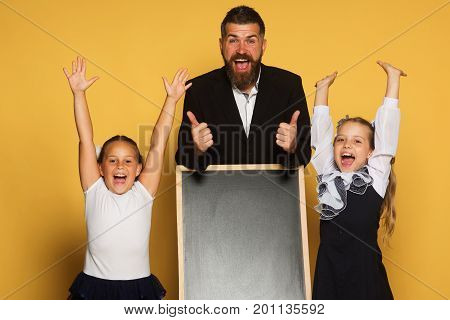 Kids With Hands Up Stand Near Blackboard. Back To School