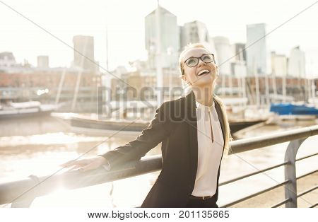 Happy business woman in suit with glasses laughing outdoors near the river in chic quater