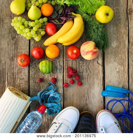 Fruits, vegetables and sports goods on wooden background.