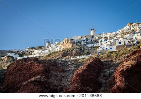 Oia Village, Santorini Cyclades islands, Greece. Beautiful view of the town with white buildings and some windmills.
