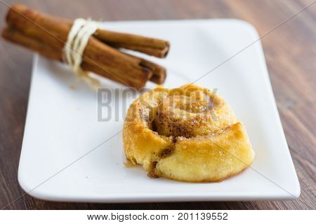 Single cinnamon roll served on white rectangle plate and decorated by a pack of cinnamon sticks