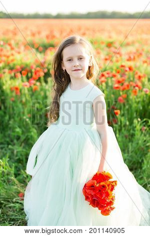 wedding, feast, beauty, kid fashion, style concept - in light of sun lovely girl with brown hair wearing fair sleeveless dress holding bunch of poppy flowers