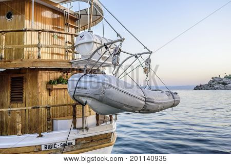 MAKARSKA RIVIERA, CROATIA - 10 JULY, 2017: A lifeboat suspended at the stern of a ship in the port.