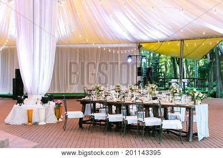 performance, wedding, party concept. beautiful space for celebrating one of the most important event, marriage. there are served tables under large tent, yellow lights and bright projectors