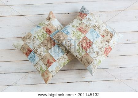 home, rest, hobby concept. two plumpy cosy pillows in pillowcases with exsquisite print consist of many square zones and prints of threes, flowers and homes