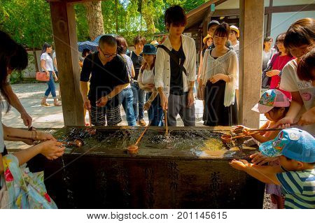 TOKYO, JAPAN JUNE 28 - 2017: Unidentified people at Kotokuin Temple in Kamakura, Japan, wash basin and dippers for washing people hands and mouths before entering the shrine.