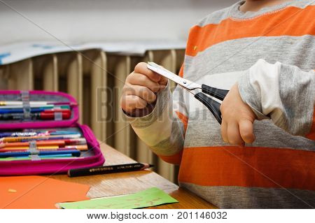 Creative child plays with safe children scissors learning to hold and use the tool.
