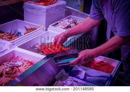 TOKYO, JAPAN JUNE 28 - 2017: Hand of a man holding a white plastic tray with red shrimps at the Fish Market Tsukiji wholesale in Tokyo Japan, Tsukiji Market is the biggest wholesale fish and seafood market in the world.