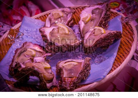 TOKYO, JAPAN JUNE 28 - 2017: Close up of a meat with a brown sauce with small slices of lemon, served over a dish with ice at the Fish Market Tsukiji wholesale in Tokyo Japan, Tsukiji Market is the biggest wholesale fish and seafood market in the world.