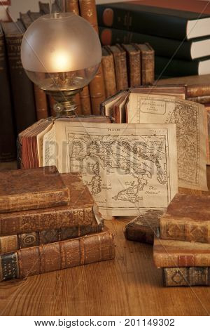 Vintage, antiquarian books pile on wooden surface in warm light with old world maps. Copenhagen, August 14, 2010