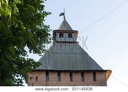 sloping wooden roof of the medieval brick tower of the 11th century the sky the branches of a tree