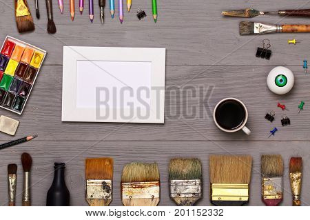 Wooden designer working table top view. Desk of an artist with lots of stationery objects. Studio shot on wooden background. Designed for easy operation. Wooden table top view of the artist.