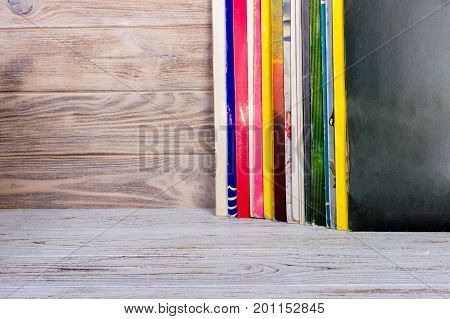 Vinyl record in front of a collection of albums. Copy space for text.