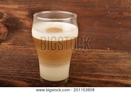 Latte macchiato on wooden table. Breakfast time. Low key photo.
