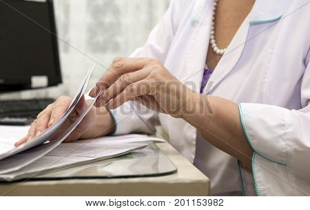 doctor medical worker paramedic in a white coat examines the table documents hand