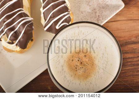 Latte macchiato and éclair. Breakfast time. Low key photo.