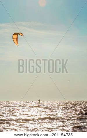 Kite-surfing on the background of sea and blue sky with clouds backlit