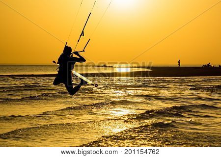 Silhouette of kitesurfer jumping over the sea on the background of gold sunset