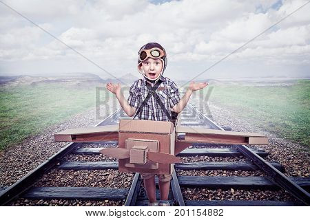 kid acting like aviator on old railway