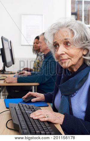 Senior Woman At Keyboard Attending Computer Class