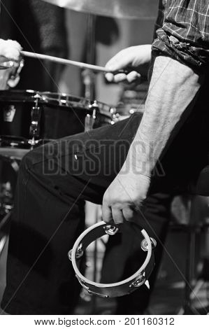 Jazz band performance. Man's hands with tambourine and drums. Black and white photography, low key image.