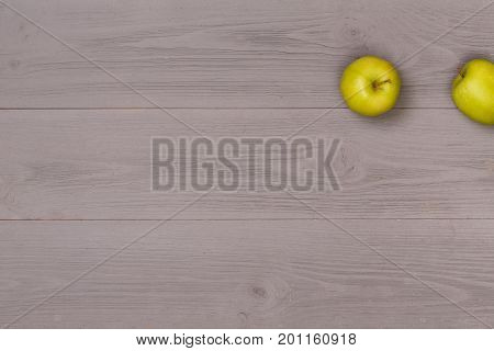 Fresh green apple on gray wooden background top view. On table food for cooking above view. Healthy food. Dietetic foods. Apple on a wooden table and a place for text