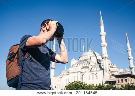 A traveler with virtual reality glasses. The concept of virtual travel around the world. In the background the blue mosque Sultanahmet in Istanbul. Modern imaging technology.