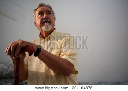 Thoughtful senior man holding walking cane while standing outdoors during foggy weather