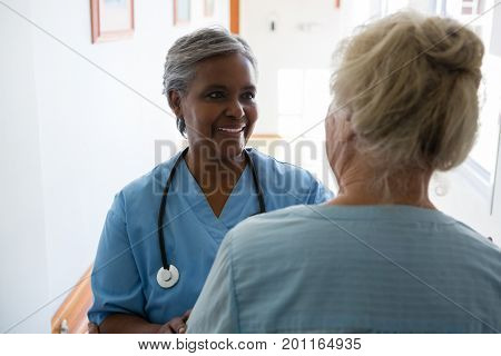 Senior woman and nurse talking while standing in corridor at nursing home