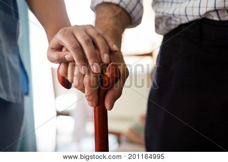Cropped hands of female doctor and senior man holding walking cane in nursing home