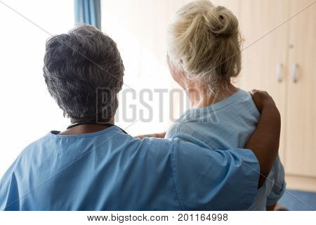 Rear view of nurse standing with senior woman in nursing home