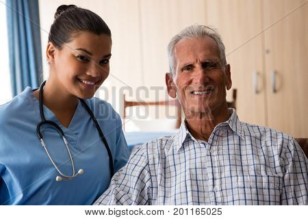 Portrait of smiling female doctor with senior man sitting in nursing home