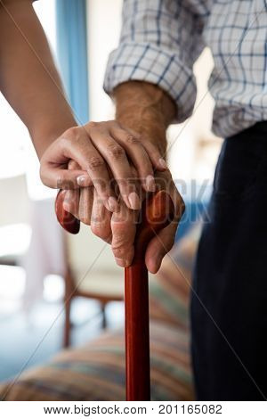 Cropped hands of female doctor and senior man holding walking cane in retirement home