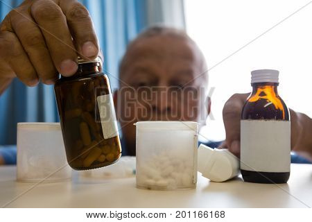 Senior man taking medicines at table in retirement home