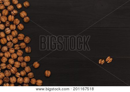 Walnut on wooden table top view. On the table are the food for cooking. Healthy food. Dietetic foods. Above view on food. Walnuts whole in their skins, chopped, nut hulls, walnut kernels