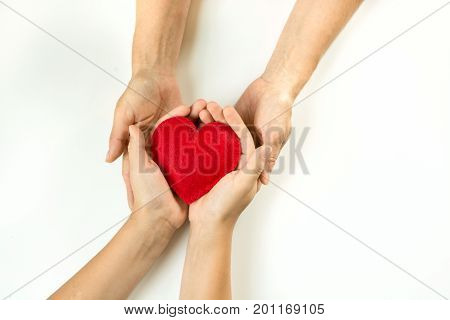 Felt red heart in childs and female hands on white background. View from above.