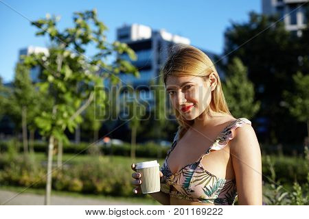 Summer portrait of stylish young woman dressed in cropped top with floral pattern having walk in park on sunny day holding papercup with her favorite hot drink looking at camera with charming smile
