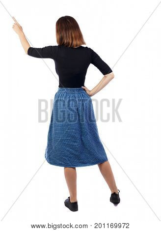 Back view of pointing woman in dress. beautiful girl. Rear view people collection.  backside view of person. Isolated over white background. A girl in a blue checkered skirt shows her hand to the left