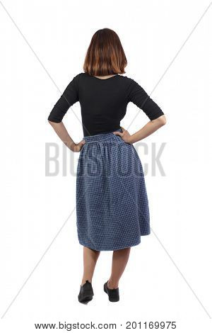 back view of standing young beautiful  woman.  girl  watching. Rear view people collection.  backside view of person. A girl in a blue skirt is standing with her hands on her hips