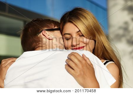 Encounter after travel or long separation. Charming young blonde woman hugging her unrecognizable boyfriend in sunglasses holding him in gentle tender manner closing eyes with enjoyment and pleasure
