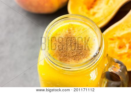 Glass mason jar with raw pumpkin butternut squash smoothie with peaches bananas spices. Ingredients on dark stone table. Bight colors top view.