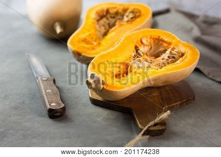Halved butternut squash pumpkin on wood cutting board. Knife and kitchen towel on dark concrete stone background. Low angle shot. Smoothie meal ingredients.