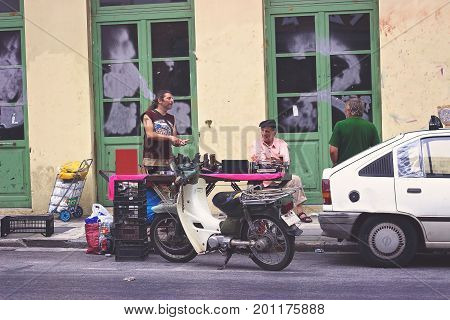 ATHENS, GREECE - JULY 16, 2017: Man bargains at flea market in Psiri area street, Monastiraki, Athens