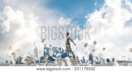 Man in casual wear keeping hand with book up while standing among flying paper documents with cloudly sky on background. Mixed media.