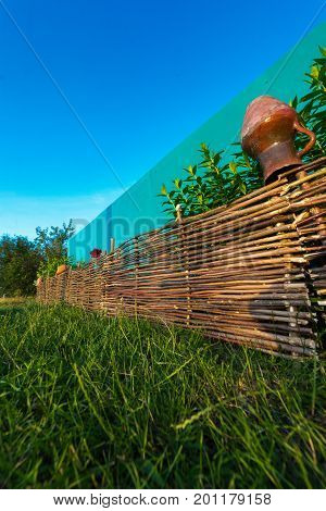 A wicker fence in nature against the blue sky.
